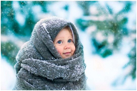 Голубоглазый ребенок, укутанный в пуховую шаль