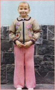 Девочка в кофточке с аппликациями и брюках